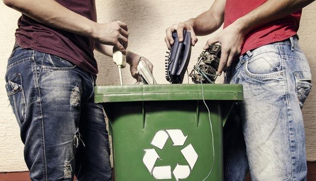 Männer entsorgen alte Elektrogeräte
