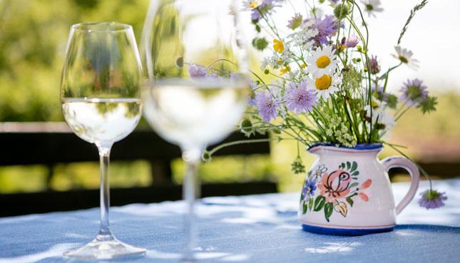 Weissweingläser auf einem sommerlich gedeckten Tisch