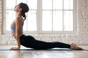 Frau macht Yoga-Übung heraufschauender Hund