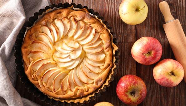 Apfelwähe, Äpfel und Wallholz auf einem Holztisch.