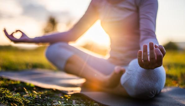 Frau meditiert auf einer Wiese.