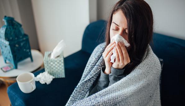 Frau mit Erkältung auf dem Sofa.