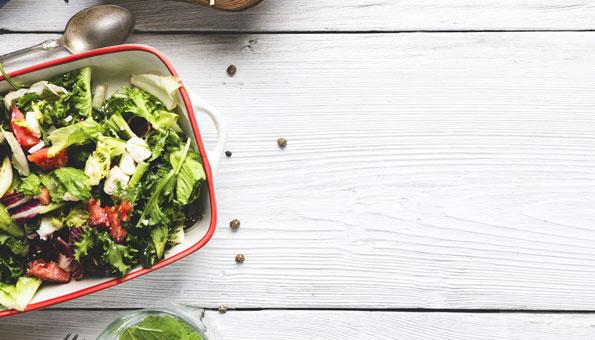 Frühlingsgemüse auf einem Holztisch: Spinat, Frühlingszwiebeln, Krautstiel, Lattich