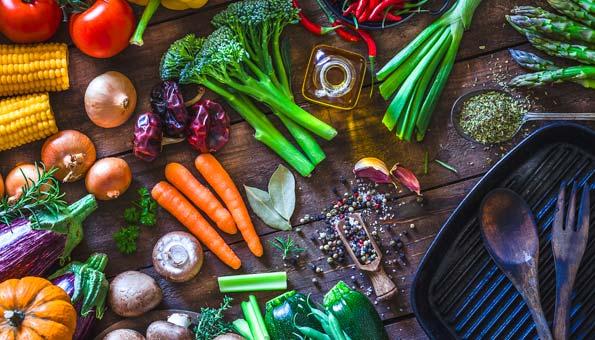 Verschiedene Gemüsesorten, Bratpfanne und Gewürze auf einem Tisch mit