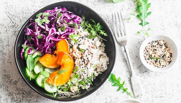 Schale mit Reis, Kürbis, Gurke und Rotkohl.