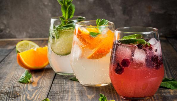 Drei erfrischende Getränke auf einem Holztisch.