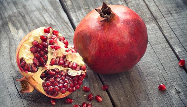 Ganzer und halbierter Granatapfel auf einem Holztisch