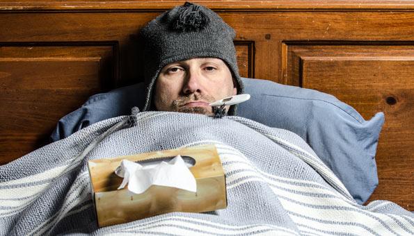 Mann mit Grippe im Bett.