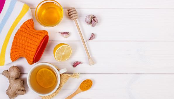 Hausmittel gegen Erkältung liegen auf einem Tisch.
