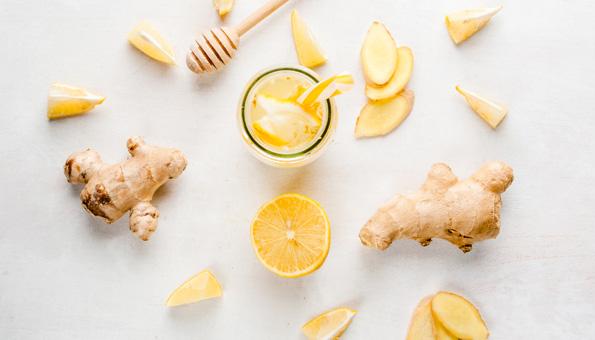 Ingwerwurzeln und Zitronenstücke mit einem fertigen Ingwergetränk