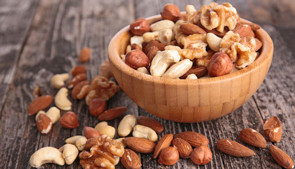 Cashew, Haselnüsse, Baumnüsse und Mandeln in einer Schale aus Holz.