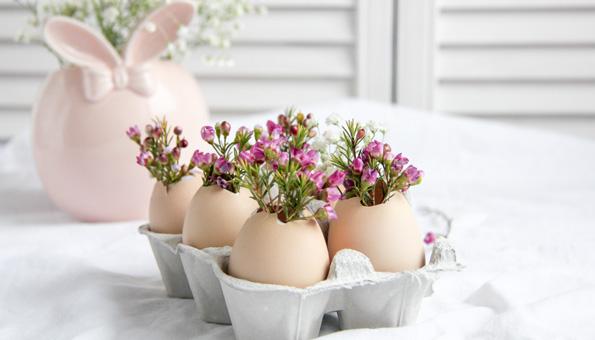 Osterdeko mit Eierkarton, Eierschalen und Blumen auf einem Tisch