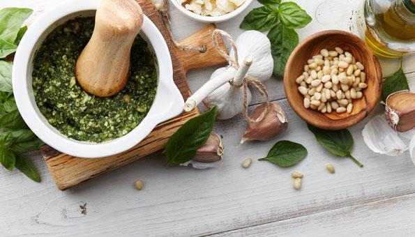 Pesto mit Basilikum, Knoblauch, Öl und Pinienkernen im Mörser mit Stössel
