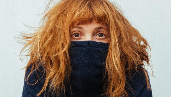 Frau versteckt Gesicht wegen Pickel