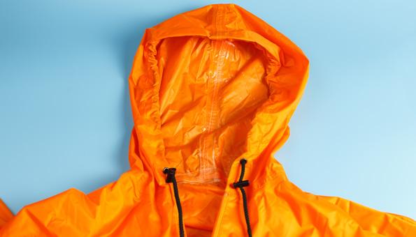 Orange Regenjacke auf blauem Hintergrund.