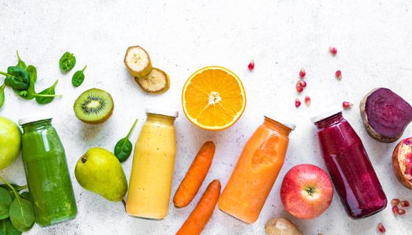 Fertige Smoothies und Zutaten wie Birne, Kiwi, Banane, Orange, Karotten, Apfel und Randen