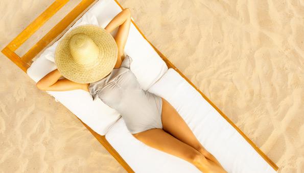 Frau im Badekleid liegt auf Liege am Strand.