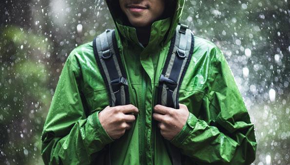 Mann trägt grüne Regenjacke im Regen.