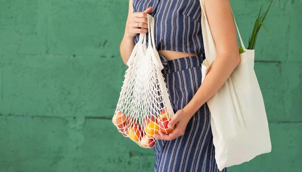 Frau mit verpackungsfreien Lebensmitteln in Einkaufstaschen.
