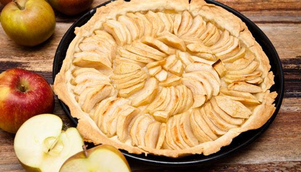 Apfelwähe im Blech auf Holztisch