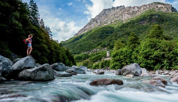 Frau am Ufer eines Flusses im Tessin.