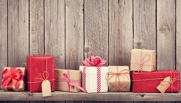 Verschiedene Geschenke in Packpapier verpackt auf einem Holztisch.