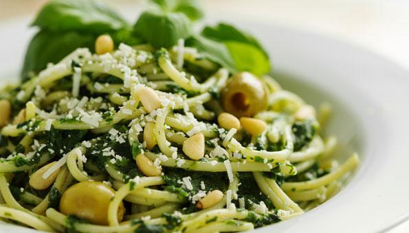 Spaghetti mit Pesto garniert mit Parmesan, Pinienkernen und Oliven