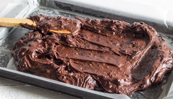 Den rohen Brownie-Teig gleichmässig auf dem Blech verstreichen.